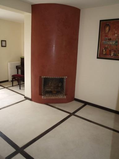 Sol en béton ciré blanc ornementé de bois exotique noir, cheminée en tadelakt.