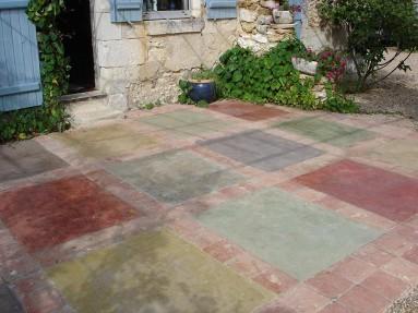 Sol en béton ciré de plusieurs couleurs ornementé de carreaux terre cuite.