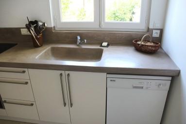 Plans de travail sur mesure en béton massif avec vasque intégrée, recouvert de béton ciré ombre calcinée.