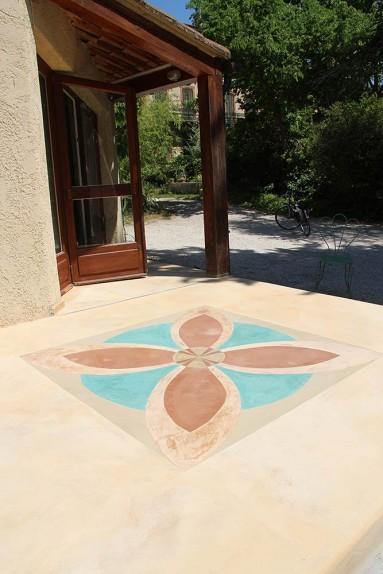 Sol en béton ciré uni, avec motifs incrustations ornementales en béton ciré de plusieurs couleurs.